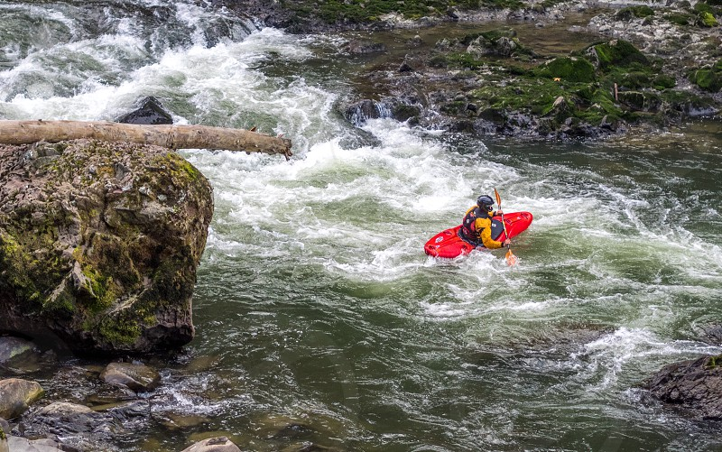 person riding red kayak on high flow current river behind gray formation rock during day time photo