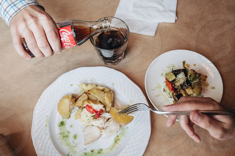 cooked food served on white ceramic round plate with a glass of coca cola soda photo