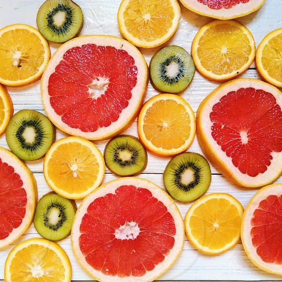 sliced red and orange citrus fruit yellow lemon and pickles photo
