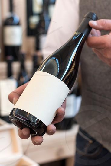 seller holding wine bottle photo