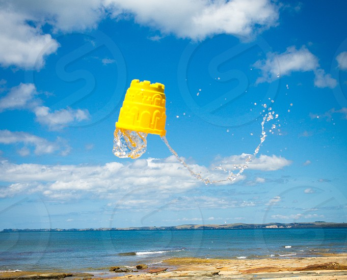Magical floating bucket at the beach against blue skies photo
