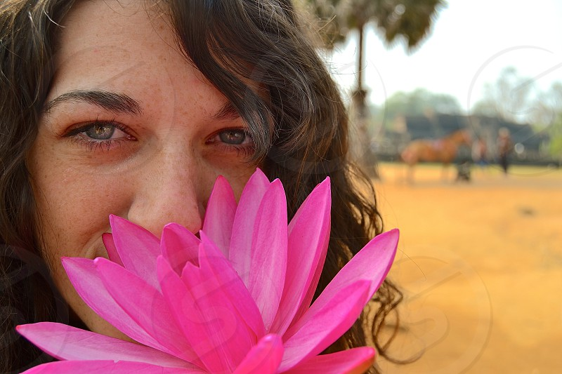 woman with green eyes smelling a pink waterlily flower selective-focus photo photo