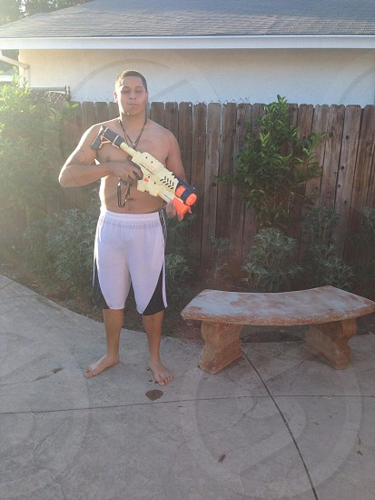 man in white and black jersey shorts holding a toy gun photo