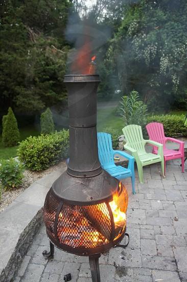 black metal wood burner spitting fire near adirondack chair outside house photo