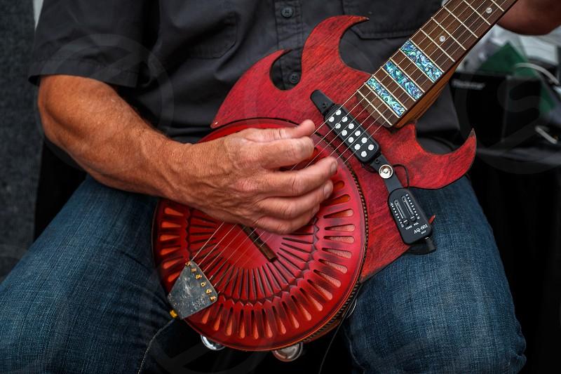 Musician plays hand made guitar at Cherry Creek Arts Festival Denver Colorado photo