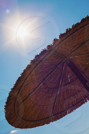 Abstract composition of sun umbrellas of reed and blue sky.  photo