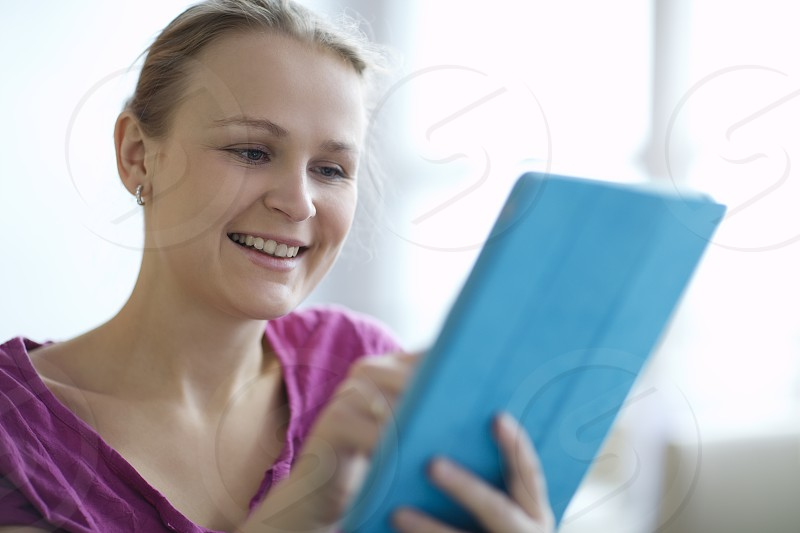 Attractive young woman smiling as she surfs the internet on a tablet computer close up head and shoulders view photo
