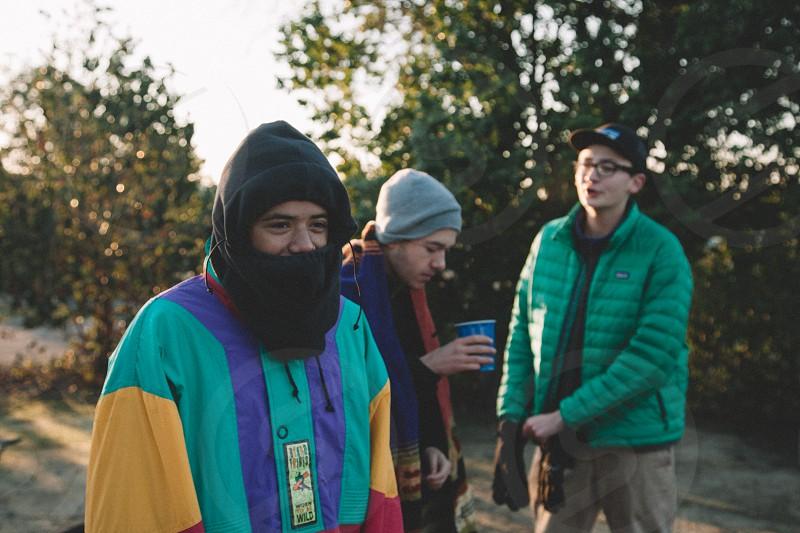 3 people wearing jacket between green trees during daytime photo