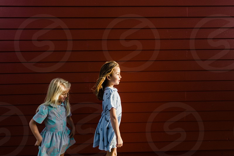 two girls next to red panels photo