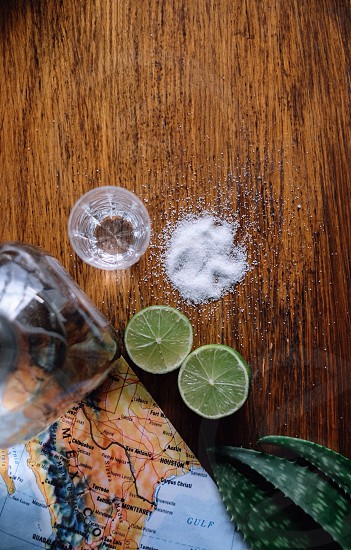 sliced lime with salt on side on brown wooden table photo