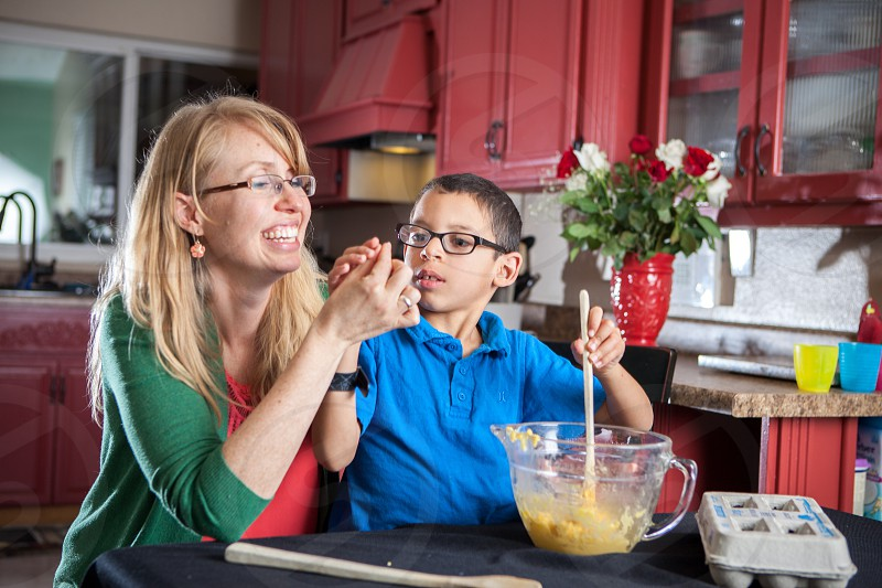 An actual diverse foster home passionate about fostering adopting loving teaching children who need a forever family. Black white mixed race happy learning kitchen table cloth blue green red glasses boy woman relating connecting together diversity. Cooking backing bowl eggs mixing food snack treat cookies dough wooden spoon. photo