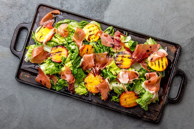 Lettuce ham serrano and grilled peaches salad served on black board. Top view. photo
