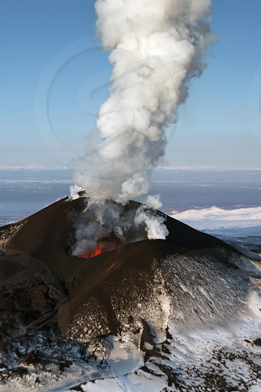 Beautiful landscape of Kamchatka Peninsula: eruption Tolbachik Volcano - effusion from the crater lava gas steam ash (view from helicopter). Eurasia Russian Far East Kamchatka Peninsula Klyuchevskaya Group of Volcanoes. photo
