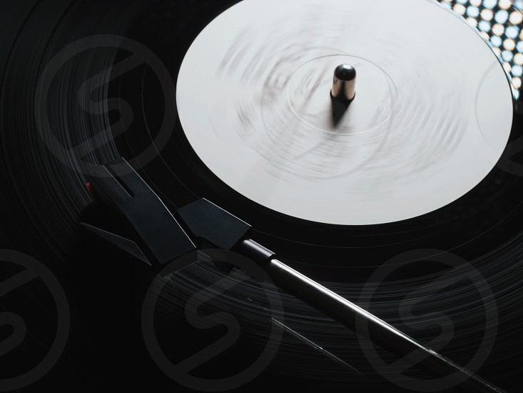 Cinemagraph retro vinyl player. Recorder on turntable viewed from above. Close-up. Pick-up lifts off. photo