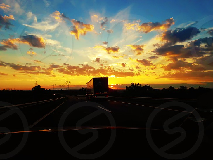 Driving on a highway behind a truck over a beautiful sunset background. Car travel holiday journey. photo