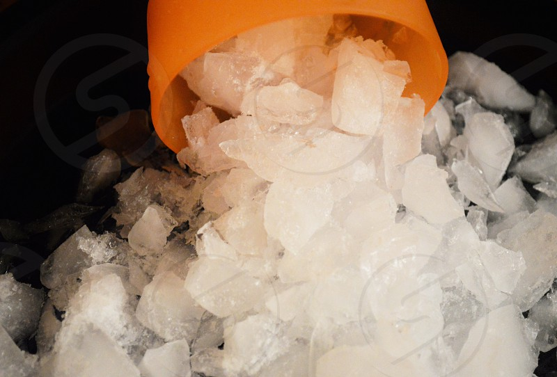 ice cubes spilled from yellow plastic drinking cup photo
