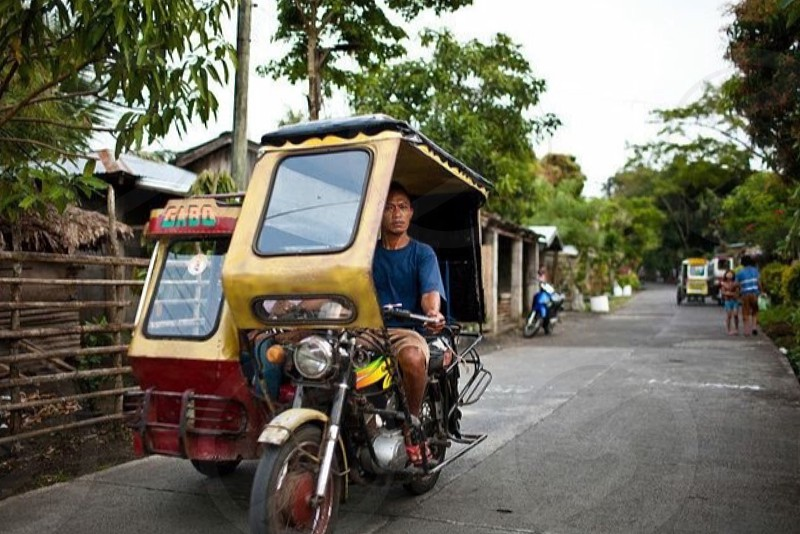 man in blue shirt driving tricycle in road photo