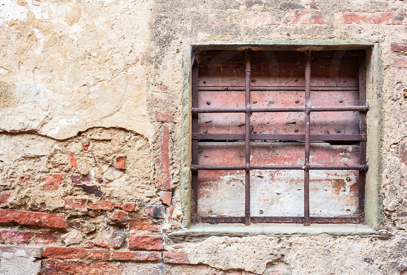 Old window with iron gratings of a house in Tuscany. photo