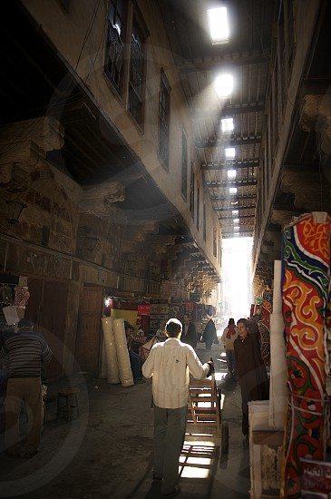 Light filters down through the street of the carpet makers in the Khan al Khalili market Cairo Egypt. photo