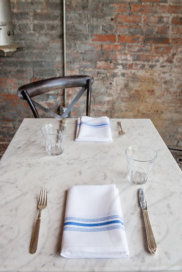 stainless steel knife and fork beside white and blue textile on white marble tile top table photo