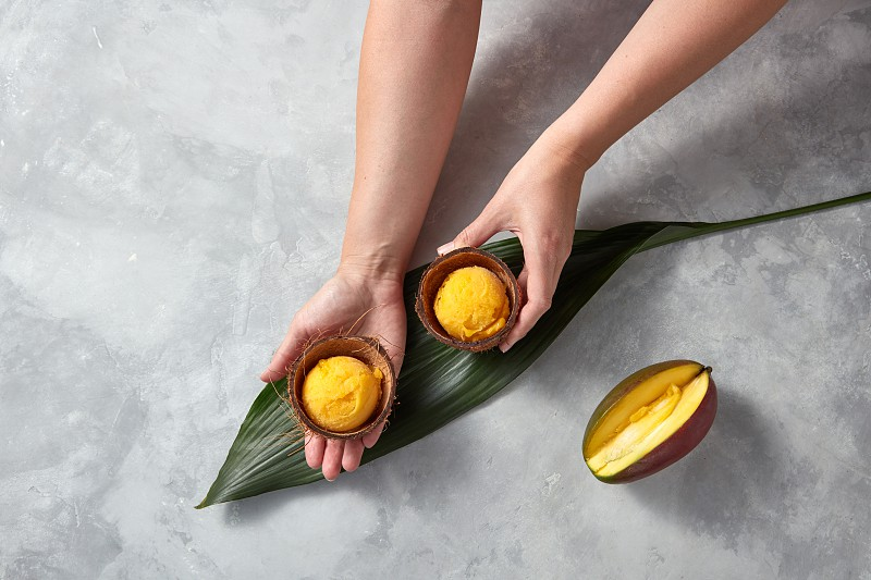Woman hands hold frozen yellow mango sorbet in the coconut shell with half fresh mango on palm leaves on gray stone background. Flat lay photo