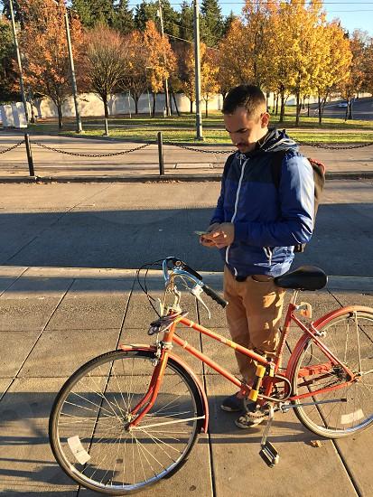man standing beside orange step-through framed bike while using his phone photo