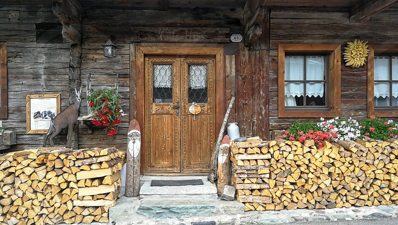 Wooden door and some firewood in front of a cabin. photo