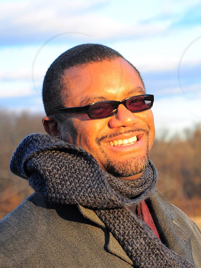 man smiling wearing a grey corset scarf black rimmed sunglasses and a grey suit photo