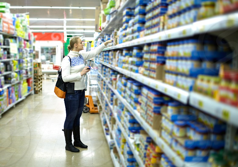 Young woman is choosing food for her child at the food store. Wide shot shallow dof. photo
