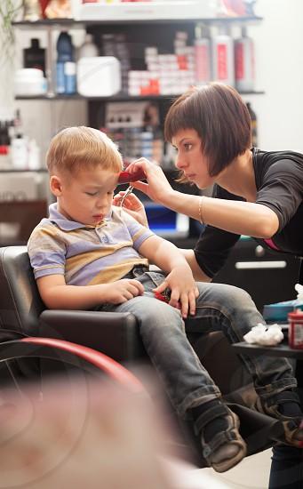 Little boy at the hairdresser sitting staring down at the floor as the stylist carefully trims his hair photo