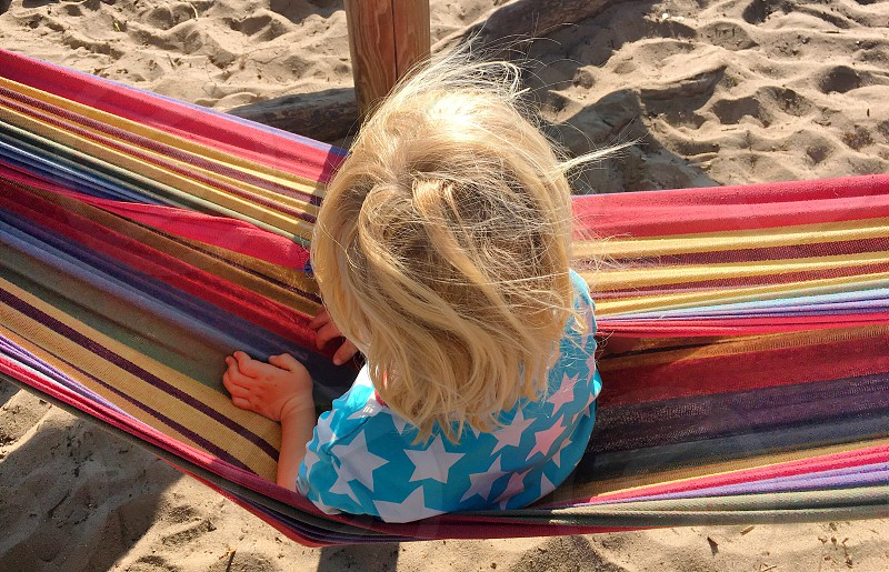 Boy blond hair hammock summer colorful lifestyle sand top view photo