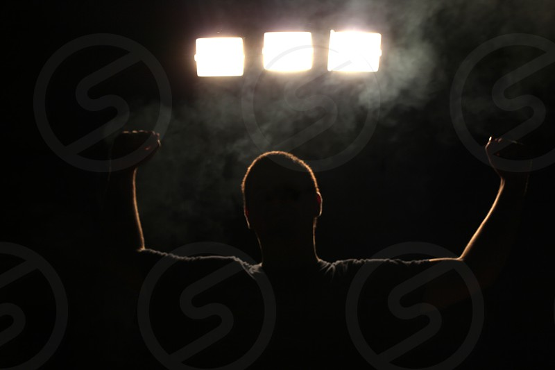 Silhouette of a happy man celebrating his victory. Fog floating around him. photo