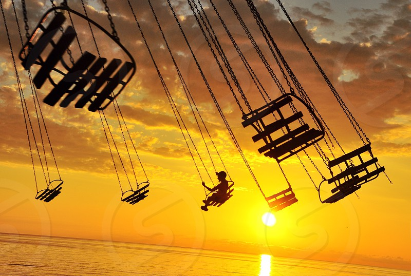 one person on swing ride at sunset photo