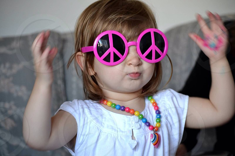 girl in magenta peace sign sunglasses with white tshirt and rainbow bead necklace photo
