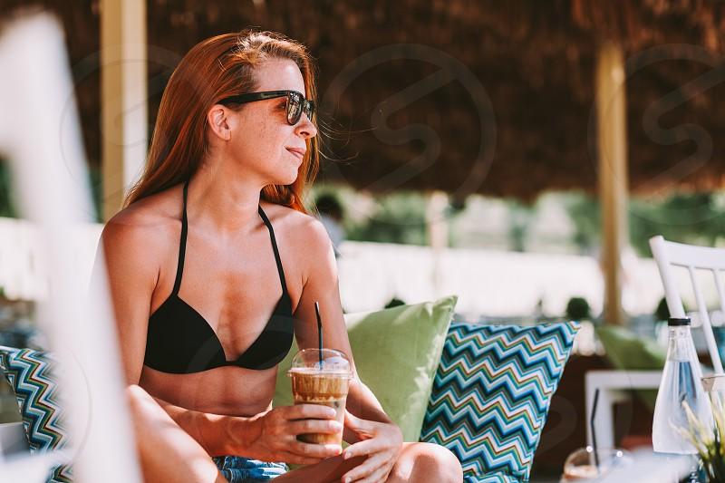 Young woman enjoying ice coffee in a beach bar photo
