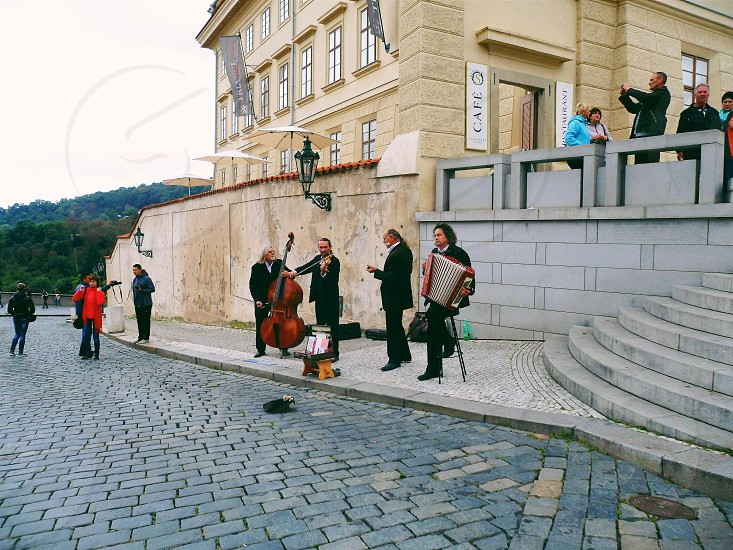 four musicians playing near the road in front of stair steps near building during daytime photo