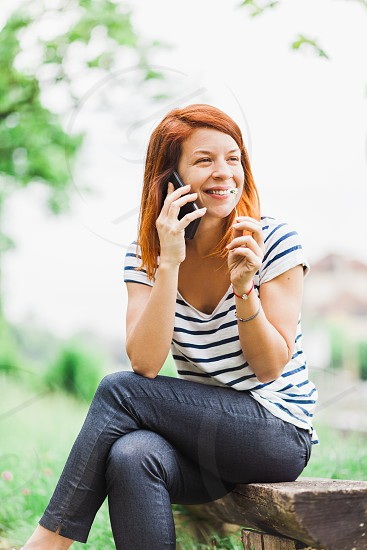 Young smiling woman talking on the phone in the park photo