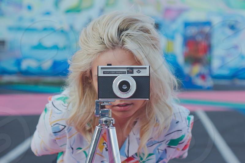 woman taking photo using silver and black digital camera photo