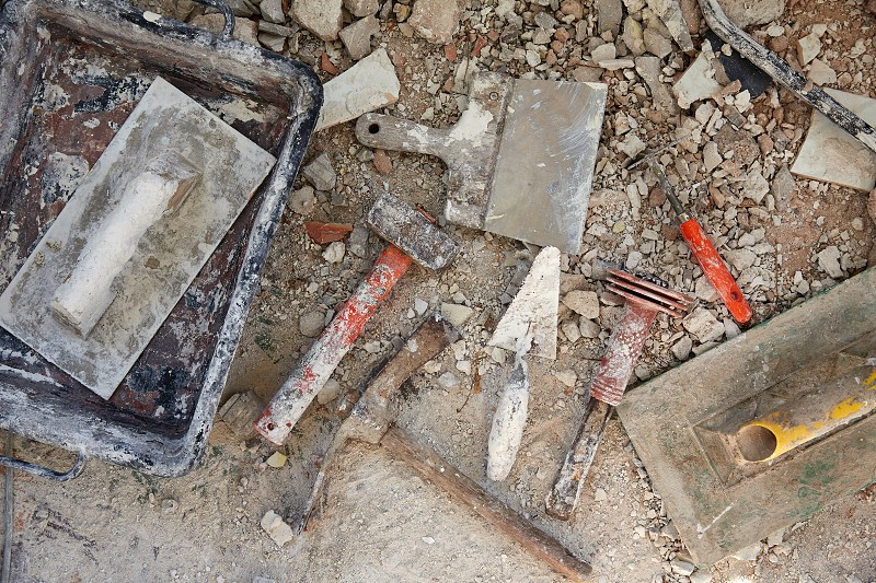 Mason tools on debris background in house improvement construction photo