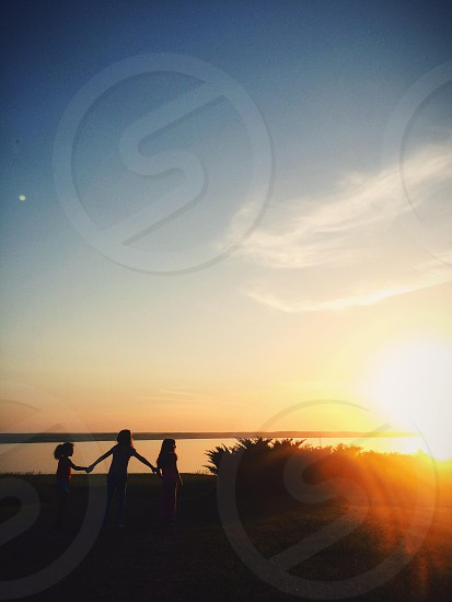 silhouette of childrens against sunset photo