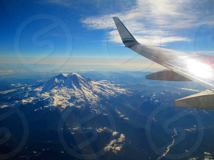 jetliner with grey wing and winglet on flight over mountains photo