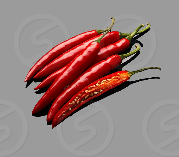 fresh red chili peppers over grey reflective surface photo