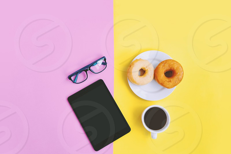 Modern home office workplace A cup of coffee donuts eye glasses and tablet on yellow pink pastel background with copy space photo