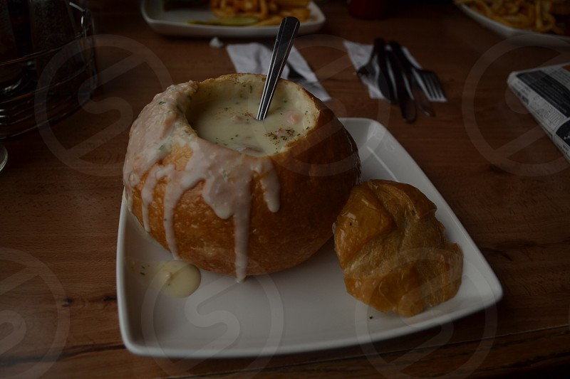 white square plate with bread bowl soup on top  photo