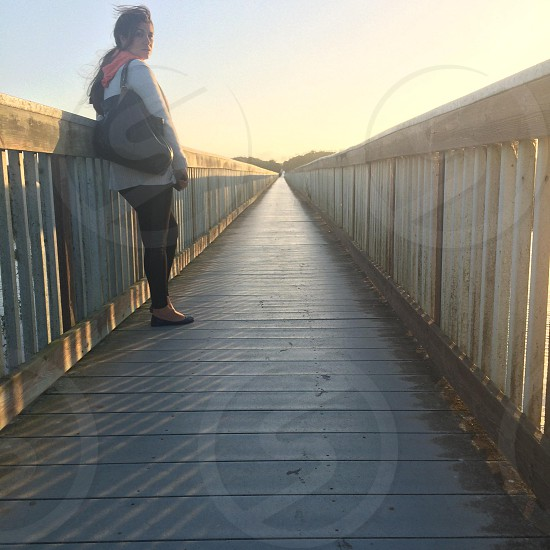 woman wearing white long-sleeved T-shirt and black fitted pants with pink scarf and black flats standing beside beige wooden foot bridge photo