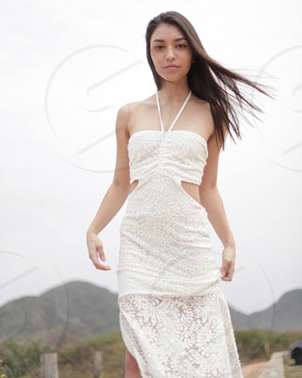 woman wearing white halter floral dress standing under white sky during daytime photo