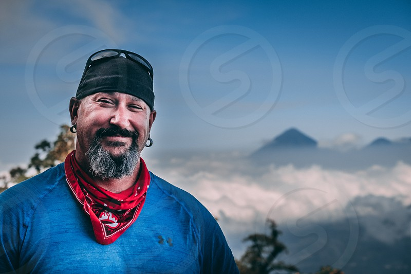 Photo of myself on top of Volcan Acatenango with the surrounding volcanoes in the background above the clouds. photo