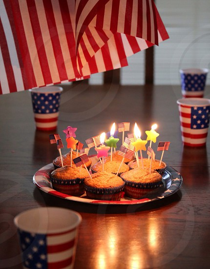 candles in assorted cupcakes surrounded by american flag paper cups photo