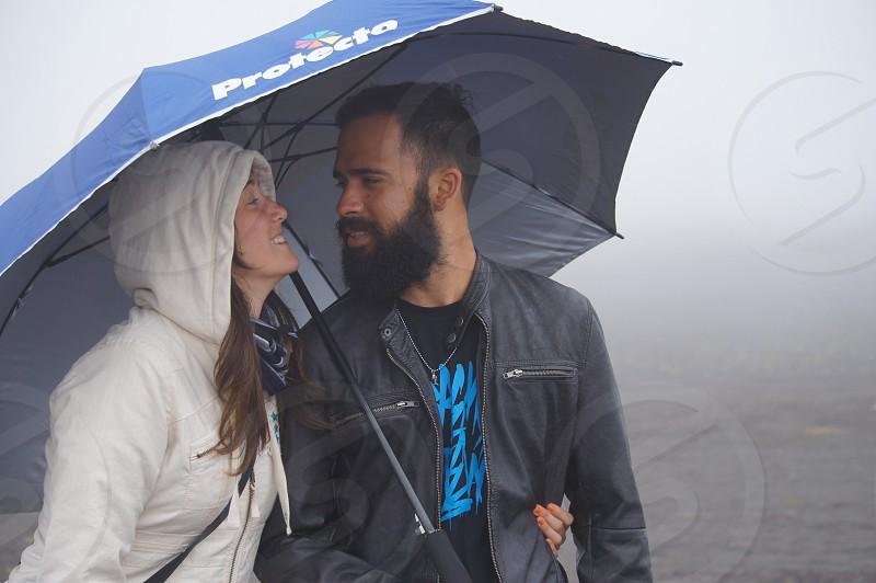 couple under blue umbrella photo