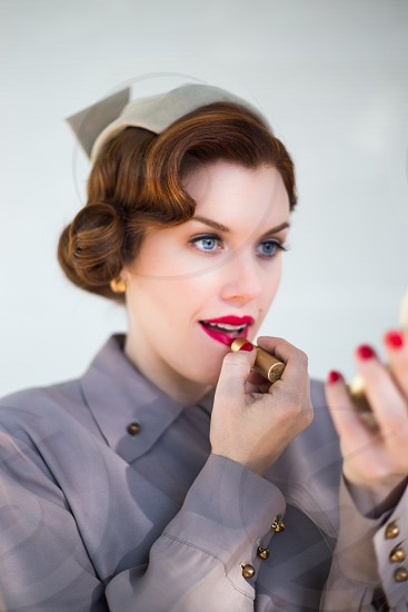 Vintage style woman applying lipstick. photo